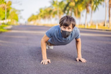Young man in medical mask performing some workouts in the park during coronavirus quarantine