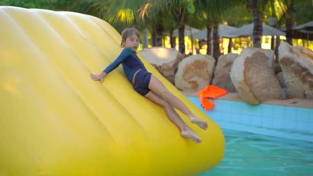 Little boy on an inflatable obstacle course in an aqua park. Summer concept. Slowmotion shot