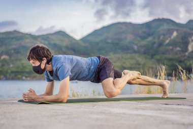Young man in medical mask performing some workouts in the park during coronavirus quarantine, Coronavirus pandemic Covid-19. Sport, Active life in quarantine surgical sterilizing face mask protection