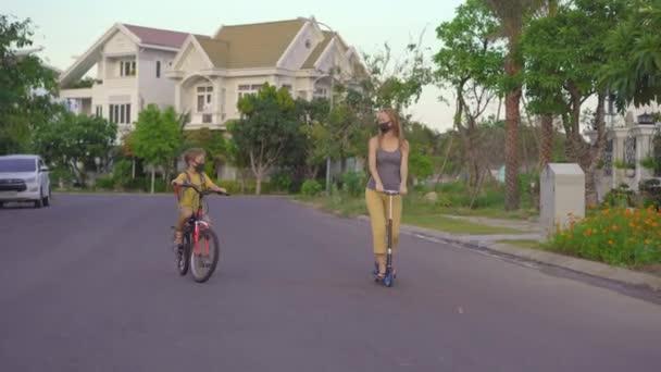 Der aktive Schuljunge und seine Mutter fahren an sonnigen Tagen Fahrrad und Roller mit Rucksack. Glückliches Kind mit dem Fahrrad auf dem Schulweg. Sicherer Weg für Kinder im Freien zur Schule. Schulen sind nach Sperrung geöffnet