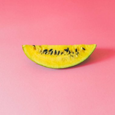 Yellow watermelon slice with seeds on pink background.