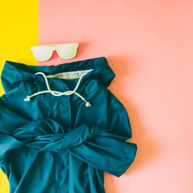 turquoise raincoat and white sunglasses on pink background. concept of fall and winter fashion