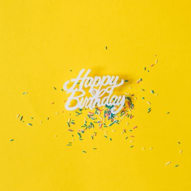 greetings happy birthday on yellow background with confetti