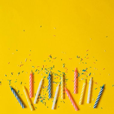 colorful candles for birthday party on yellow background