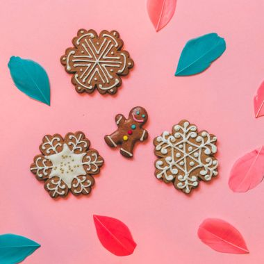 cookies in the shape of snowflakes and the gingerbread man among the colored feathers on a pink background. happy new year and merry christmas
