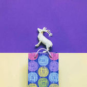 Fotografie Christmas gift bag and white deer on ultra violet and yellow background