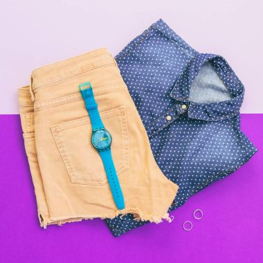 women set with accessories: denim polka dot shirt, watch, two silver rings and shorts