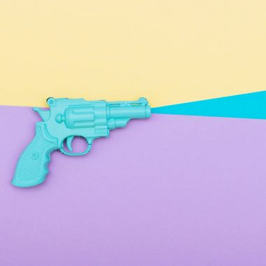 blue plastic gun on colored background