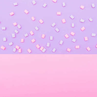 colorful marshmallow laid out on blue and pink background
