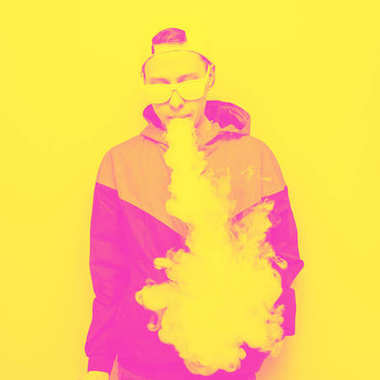 Young man in sunglasses vaping on yellow background