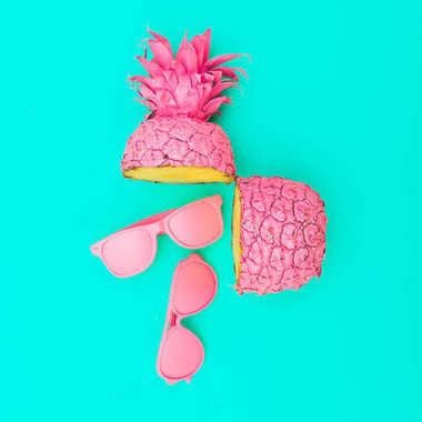 Two painted in pink color halves of pineapple with pink sunglasses on turquoise background.