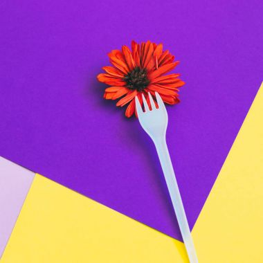Plastic fork with orange flower on yellow and  purple background of paper textures. Minimal flat lay