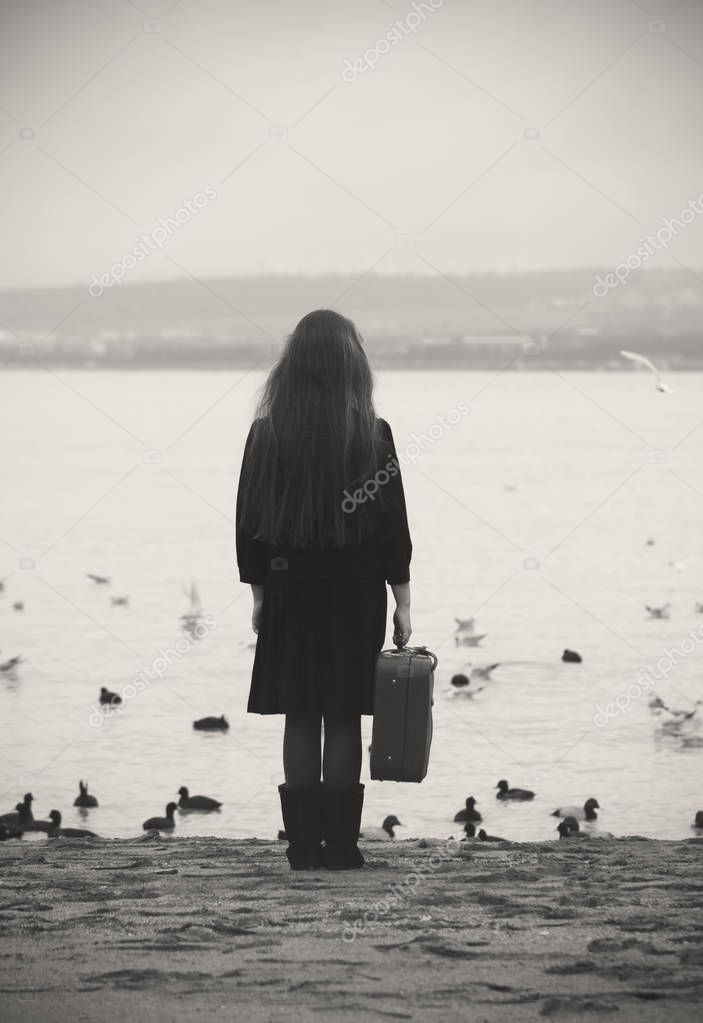 a girl with a suitcase stands and looks at the sea around birds fly