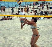 Girl in bikini playing beach volleyball