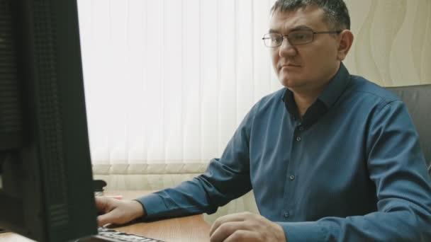 Věci v kanceláři: portrét člověka v brýlích pracující na počítači, zblízka
