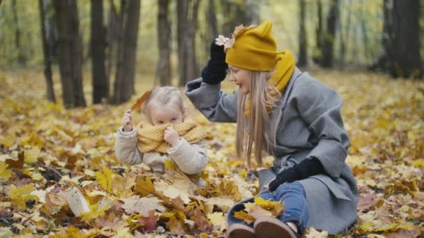 Mother and her daughter little girl walking in a autumn park - mommy and child have fun and buried in the yellow leaves