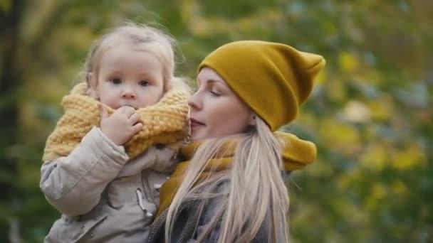 Matka a její dcera holčička hraje v podzimním parku - Maminka a dítě bavit a předení, zblízka