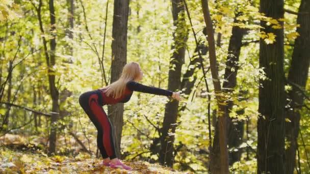 Mädchen, das einen Training Work-Out im Herbst Park. Blonde sexy Fitness-Bikini-Model im roten Anzug und rosa Turnschuhe