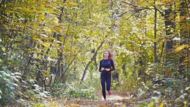 Fiatal futó lány van, jogging a lehullott levelek őszi országutat. Sport egészséges életmód fogalma, lassú mozgás