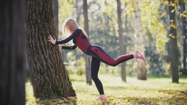 Fitness žena silový trénink dělá cvičení na slunné podzimní park. Přizpůsobit kavkazské sportovní dívka výkonu její tělo poblíž stromu - výtahy nohy střídavě, Zpomalený