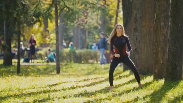 Fitness woman strength training doing workout at sunny autumn park. Fit caucasian sporty girl exercising her body - doing squats