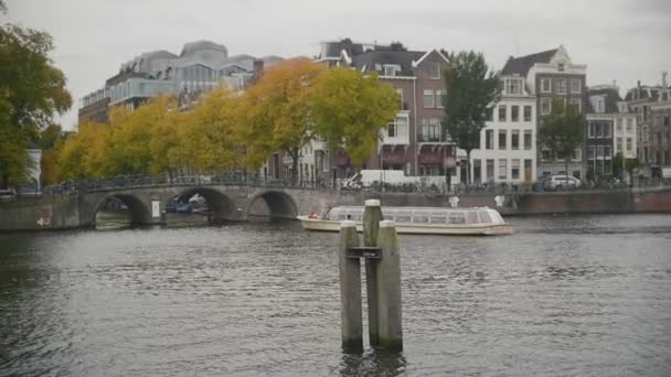 Tour boat sails in Amsterdam canal, Holland, Netherlands, slow motion