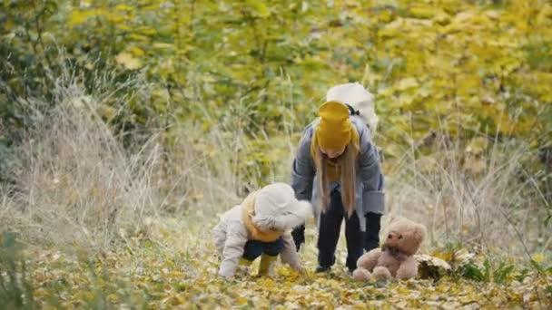Malá dcera s matkou si hraje s žluté listí v podzimním parku