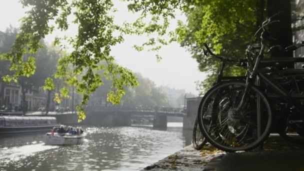 Pohled na kola bicyklu na Amsterdam amstel canal, dále na plováky výletní loď, sunny Evropský podzim