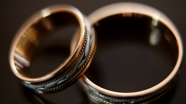 Golden wedding rings on mirror glasses table - one lies top of another, macro