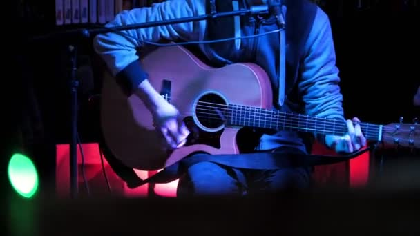 Guitarist plays acoustic guitar and sings microphone in night club, blue  lights, close up