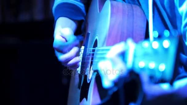 Zblízka pohled kytarista hraje akustická kytara v nočním klubu