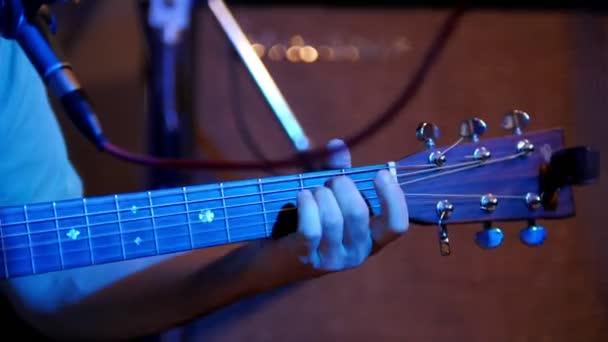 Musician playing acoustic guitar - guitar soundboard, telephoto