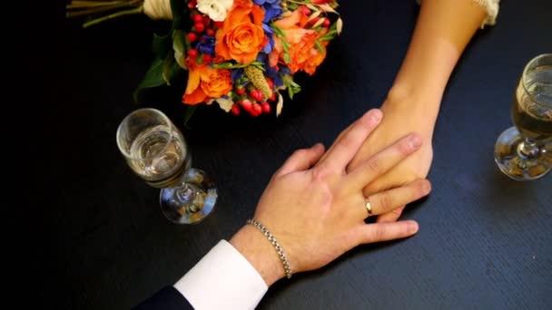 Mans a žena ruce na stůl v kavárně - svatební koncept