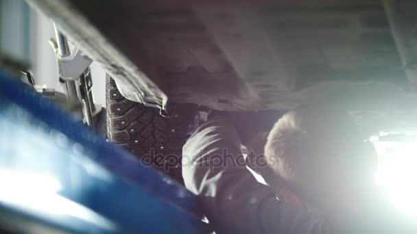 Auto servis - mechanik odšroubování dílů při práci pod zvednuté auto