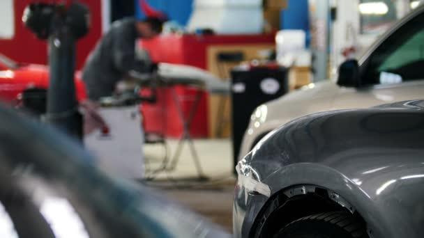 Autószerviz, rögzítése és javítása autó, defocused háttér részlete szerelő