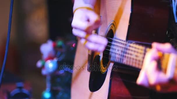 Kytarista drží akustická kytara poblíž mikrofon na koncertě v klubu, extrémně detailní záběr
