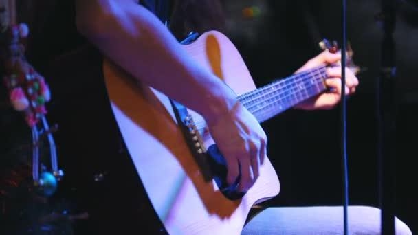 Kytarista drží akustická kytara poblíž mikrofon na koncertě v klubu