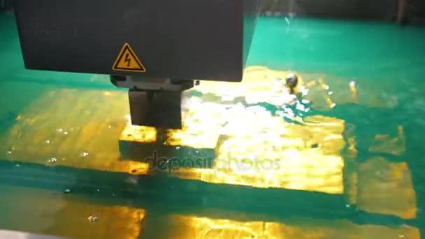 Řezání plechu procesu ve vodě. Jiskry létají z laserové automatické továrny, výrobní, pohled zepředu