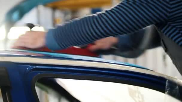 Automobilové služby - pracovník leští modré auto, boční pohled