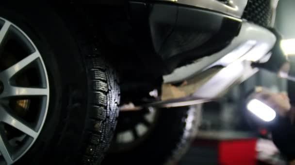 Auto servis - mechanik rezervaci automobilových dílů při práci s lampou, de-zaměřil pozadí