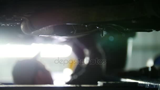 Autó-service - szerelő tartószerkezethez automobile részek alatt egy felemelt automatikus, munka közben defocused háttér