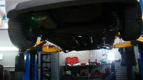 Automobile car diagnostic - mechanic working under a lifted car, slider