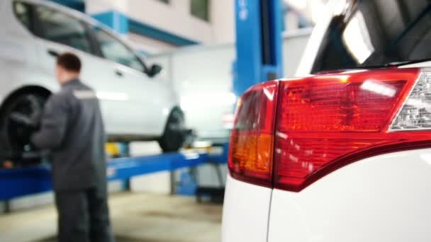 Detaily vozu - auto světlometů zblízka v diagnostické služby - mechanik práci v blízkosti zvednutého auta