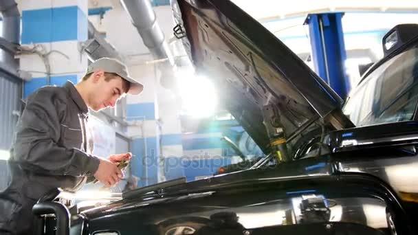 Szerelő férfi autó garázsban ellenőrzése a motorháztető az autó, a luxus Suv