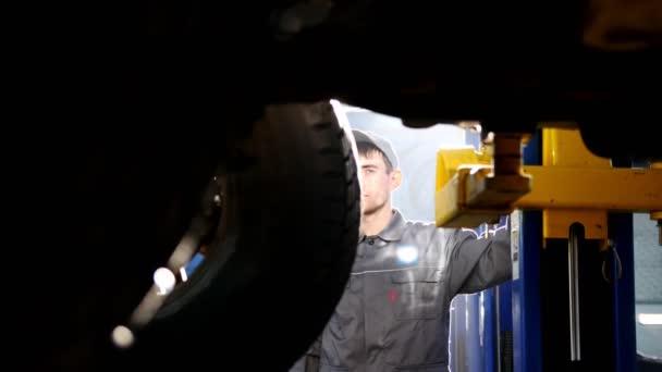 Mechaniker hebt Geländewagen in Kfz-Werkstatt - Rad