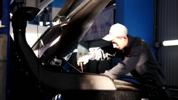 Szerelő férfi unscrews egy csavarhúzóval, a motorháztető az autó SUV