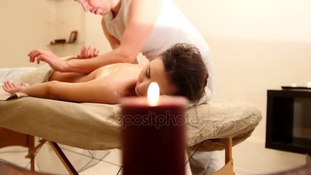 Atraktivní mladá žena přijímá olejová masáž v lázních
