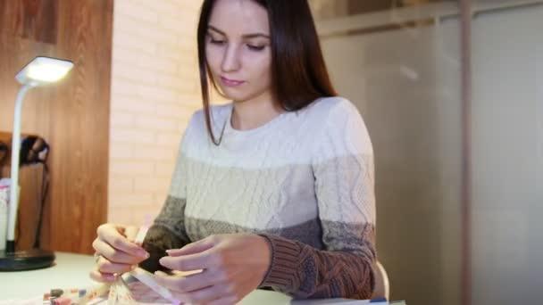 Mladá žena si vybere barvu a texturu hřebíků v profesionální manikúra salon krásy, jezdec