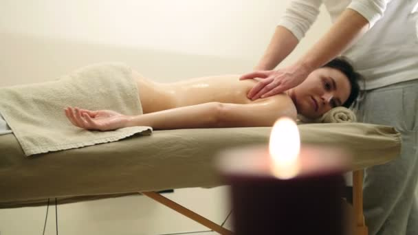Vonzó fiatal nő kap a wellness-részlegben masszázs. Relaxációs kezelés a váll, csúszik