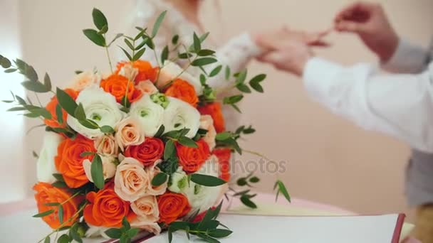 Bellezza sposa e sposo bello indossano anelli dorati vicenda davanti al bouquet da sposa. Cerimonia di matrimonio